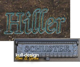 Schrift in Metallplatte graviert, Kontur mit Farbe ausgelegt.